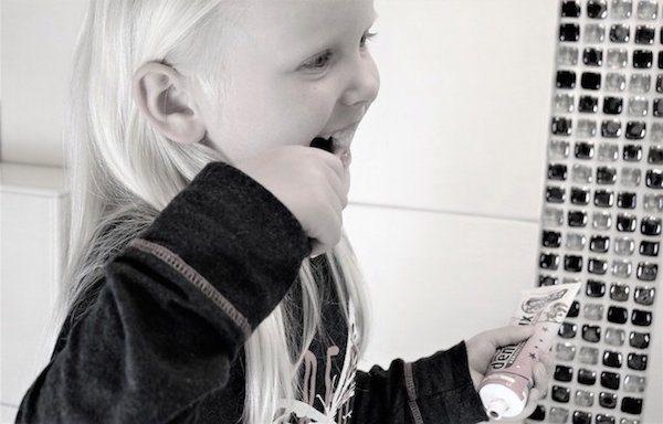 歯磨き粉を持って1人で歯を磨く子ども
